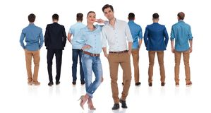 Young casual couple standing behind their male colleagues royalty free stock image