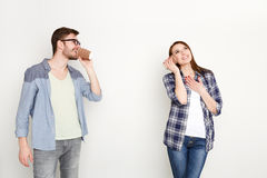 Young casual couple talking through tin can phone Royalty Free Stock Photography