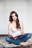 Young casual female holding red book. Natural light portrait of young brunette caucasian girl in white casual clothing which sitting on the plaid and holding stock images
