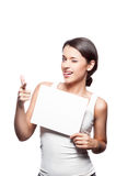 Young casual girl holding sign with funny face. Studio portrait of young attractive casual brunette caucasian female girl holding blank white sign and pointing Royalty Free Stock Image