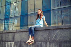 Young casual girl looking far away while sitting against a busi Stock Photography