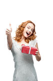 Young casual girl with red gift showing thumb-up. Young red-haired casual girl with red gift looking at camera with nice toothy smile and showing thumb-up stock photography
