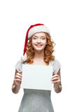 Young casual girl in santa hat holding sign. Young casual happy smiling caucasian girl in santa hat looking at camera and holding sign stock photography