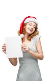 Young casual girl in santa hat holding sign. Young casual happy smiling caucasian girl in santa hat looking at camera and holding sign royalty free stock photography