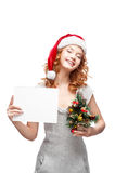 Young casual girl in santa hat holding sign. Young casual happy smiling caucasian girl in santa hat looking at camera and holding sign and christmas treern royalty free stock images