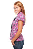 Young casual girl standing in profile and smiling. In studio Stock Images