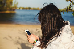 Young casual girl using  mobile phone on beach Royalty Free Stock Photography
