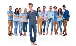 Young casual group leader welcomes you in his team. Young casual group leader with glasses welcomes you in his team with both hands while standing on white stock photos