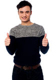 Young casual guy gesturing double thumbs up Stock Images