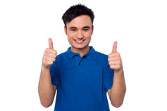 Young casual guy gesturing double thumbs up Stock Photos
