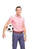 Young casual guy holding a football Royalty Free Stock Photography
