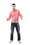 Young casual guy in plaid shirt with thumbs up gesture Royalty Free Stock Images