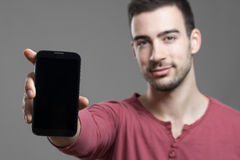 Young casual happy man in red shirt showing black blank smart phone screen at camera Royalty Free Stock Photos
