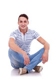 Young casual happy man seated Royalty Free Stock Images