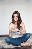 Young casual happy smiling girl with cell phone. Natural light portrait of young casual happy smiling caucasian brunette girl with cell phone Stock Photos