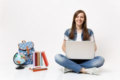 Young casual joyful smiling woman student holding using laptop pc computer sitting near globe, backpack, school books. Isolated on white background. Education royalty free stock photography
