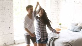 Young couple dancing in bedroom, performing twist rock and roll