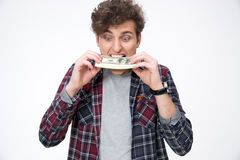 Young casual man biting money royalty free stock image