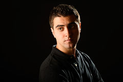 Young casual man on black background Stock Photos
