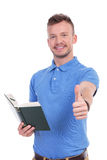 Young casual man with book shows thumb up. Casual young man holding a book and showing the thumb up gesture to the camera, with a smile on his face. on a white Royalty Free Stock Image