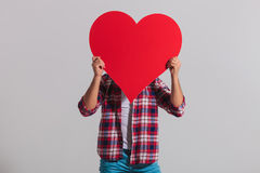 Young casual man covers his face with big red heart. On grey studio background Royalty Free Stock Photos