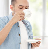 Young casual man drinking a cup of tea Stock Photo