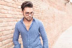 Young casual man with glasses looks down Royalty Free Stock Photo