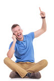 Young casual man on his phone points up Stock Images