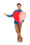 Young casual man holding big heart and presenting. Full body picture of a young casual man holding big heart and presenting something on white background Royalty Free Stock Images