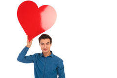 Young casual man holding big red heart in the air. Above his head on white background Royalty Free Stock Photo