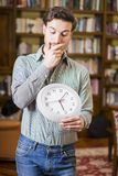 Young man scared of time holding clock. Young casual man holding clock and looking pressed with time limit posing ine Stock Image