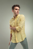 Young casual man holding his right arm Royalty Free Stock Image