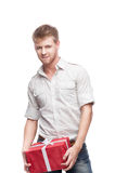 Young casual man holding red gift. And looking at camera isolated on white stock image