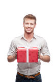 Young casual man holding red gift. And nice toothy smiling at camera isolated on white stock images