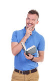 Young casual man holds book and smiles pensively Stock Image