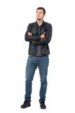 Young casual man in jeans and leather jacket with crossed arms looking up. Full body length portrait isolated over white background stock photos