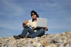 Young casual man with laptop. At the beach royalty free stock image