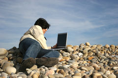 Young casual man with laptop at the beach. Isolated on blue sky background royalty free stock images