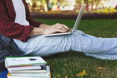 Young casual man with laptop outdoors. Male student preparing for exams with computer and books in the park. Education and entering the university concept Stock Photos