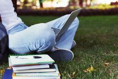 Young casual man with laptop outdoors. Unrecognizable male student preparing for exams with computer and books in park. Education and entering university Royalty Free Stock Images