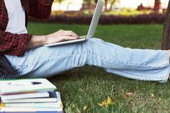 Young casual man with laptop outdoors. Unrecognizable male student preparing for exams with computer and books in park. Education and entering university Royalty Free Stock Photos