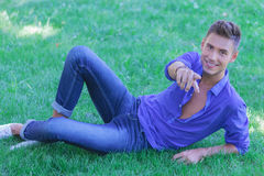 Man resting on ground and pointing Royalty Free Stock Photos