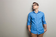 Young casual man leaning his head on a grey wall. Stock Photography