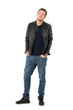 Young casual man in leather jacket and blue jeans with smirk smile tilting head. Full body length portrait isolated over white studio background Royalty Free Stock Photos