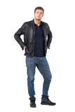 Young casual man in leather jacket put hands in pockets looking at camera Royalty Free Stock Image