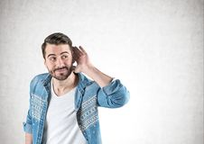 Young casual man listening, concrete wall. Portrait of smiling young man with beard in casual clothes listening attentively with his hand near ear. Concrete wall royalty free stock image