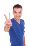 Young casual man making victory sign Royalty Free Stock Images