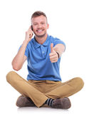 Young casual man on the phone shows thumb up Royalty Free Stock Photo