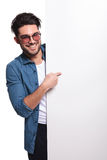 Young casual man pointing to a empty board Stock Photos