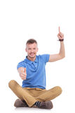 Young casual man points up and gives thumb up Stock Photo